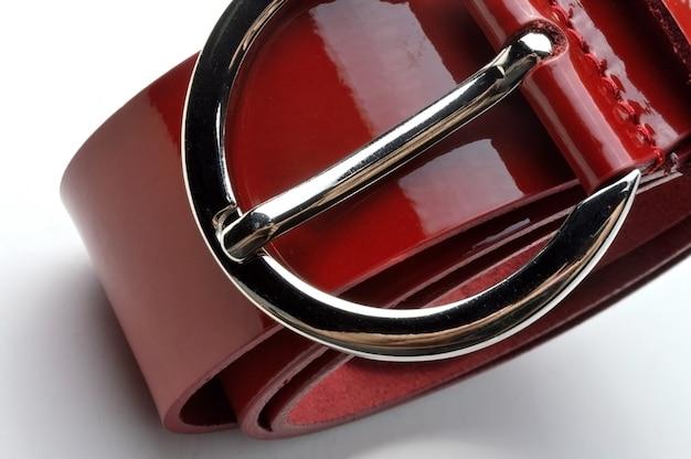 Cinto feminino trançado, vermelho, brilhante, com placa cromada. em um close-up de fundo branco.