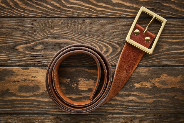 Cinto marrom largo masculino feito de couro genuíno com fundo de madeira