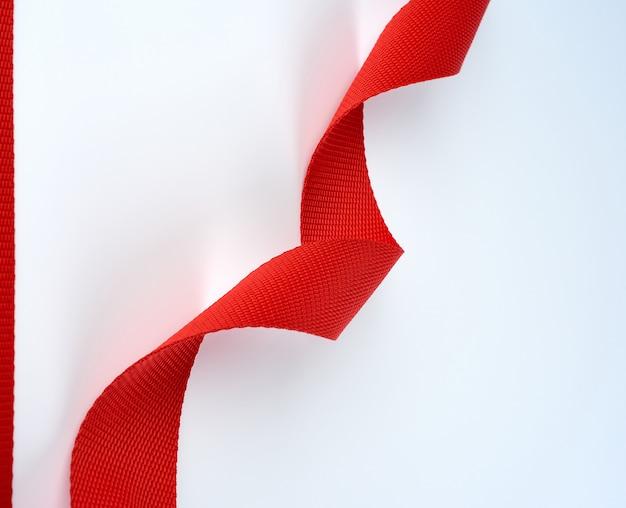 Cinto têxtil vermelho trançado com uma fibra grossa sobre um branco
