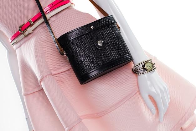 Cintos e bolsa no manequim. manequim feminino com acessórios elegantes. cintos brilhantes e bolsa escura. bolsa vintage com cintos.