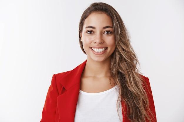 Cintura bem-sucedida sortuda atraente mulher européia vestindo jaqueta vermelha sorrindo dentes brancos mantendo-se positiva, sentindo-se otimista recebendo promoção, atingindo a meta, recebendo elogios, parecendo satisfeita