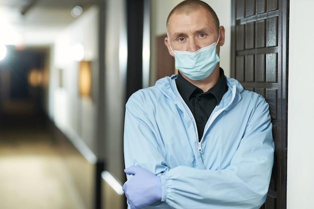 Cintura de homem com máscara protetora em pé no corredor do hotel. coronavírus e conceito de quarentena. copie o espaço