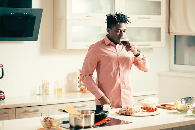 Cintura de jovem em pé na cozinha com uma taça de vinho tinto