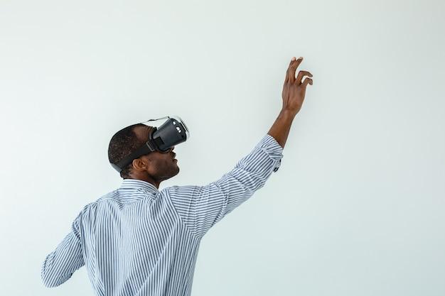 Cintura de um homem afro-americano simpático usando uma prancha enquanto testa os óculos de realidade virtual
