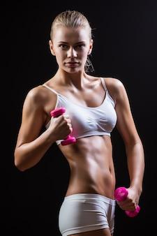 Cintura e mãos de uma linda mulher musculosa e esportiva malhando com dois halteres, isolados contra um fundo preto