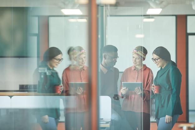 Cintura gráfica para cima retrato de três empresários contemporâneos discutindo trabalho em pé atrás de uma parede de vidro no escritório, copie o espaço