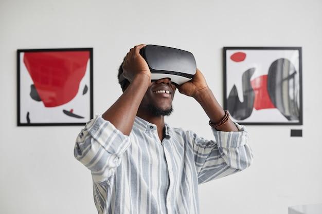 Cintura gráfica para cima retrato de um homem afro-americano sorridente usando equipamento de rv enquanto desfruta de uma experiência imersiva na exposição da galeria de arte moderna,