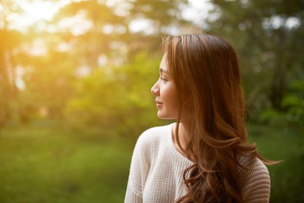 Cintura lateral para cima tiro de mulher se afastando da câmera para olhar o pôr do sol