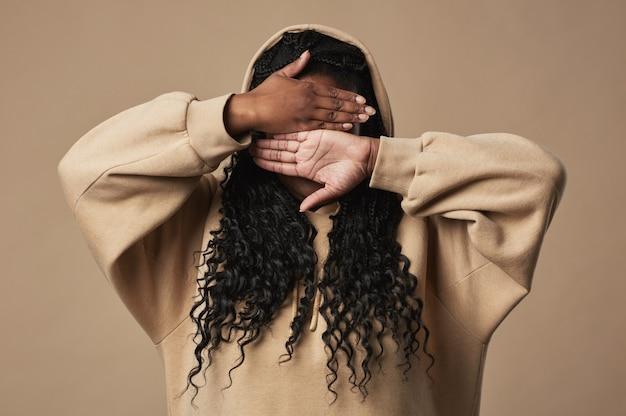 Cintura mínima para cima retrato de uma jovem afro-americana escondendo o rosto enquanto posava em um fundo bege neutro em estúdio, copie o espaço