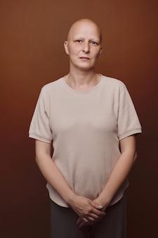 Cintura mínima para cima retrato de uma mulher careca olhando para a câmera enquanto posava em um fundo simples em estúdio.