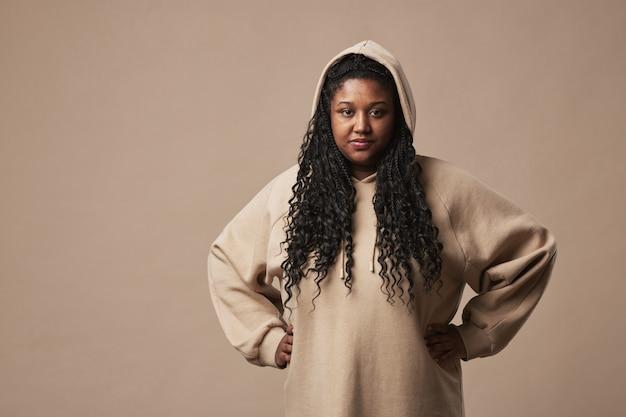 Cintura mínima para cima retrato de uma mulher curvilínea confiante olhando para a câmera e vestindo um capuz confortável em pé contra um fundo bege neutro no estúdio, copie o espaço