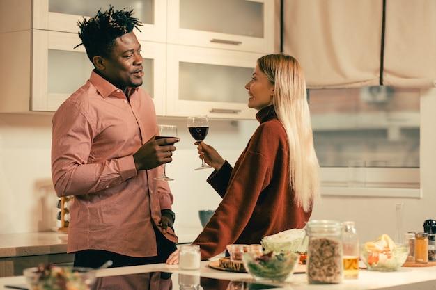 Cintura para cima de mulher de cabelos compridos em pé de costas para a mesa e sorrindo para o namorado enquanto bebia vinho com ele