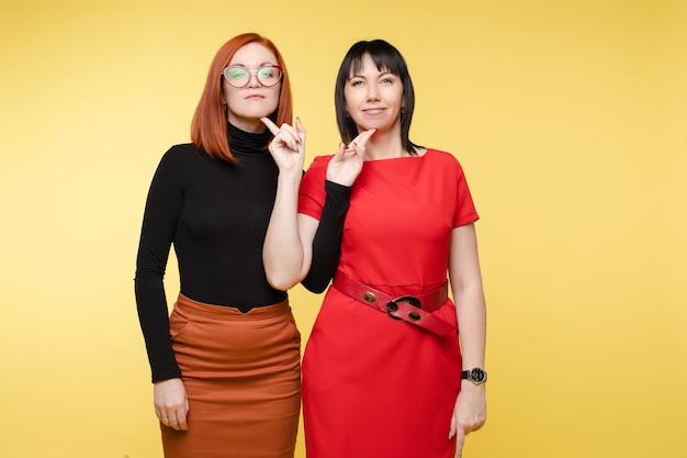 Cintura para cima de mulheres bonitas tocando-se com os dedos no queixo uma da outra. isolado em fundo amarelo