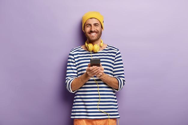 Cintura para cima de um hipster atraente feliz usa fones de ouvido estéreo e segura um celular moderno, escuta a faixa de áudio e verifica a notificação, vestido com um macacão de marinheiro listrado