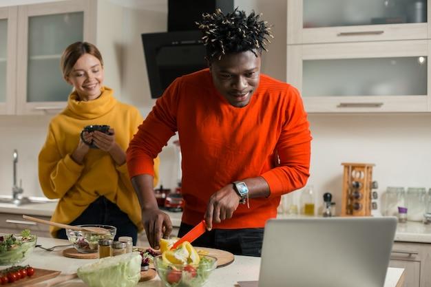 Cintura para cima de um jovem calmo olhando para a tela do laptop e cortando colorau amarela enquanto sua namorada alegre fica atrás dele com uma xícara de chá