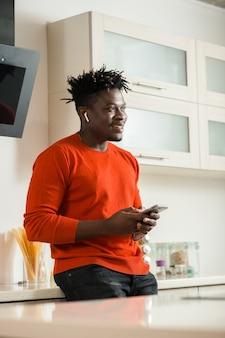 Cintura para cima de um jovem positivo usando fones de ouvido sem fio e parecendo feliz em pé na cozinha com um smartphone moderno e sorrindo