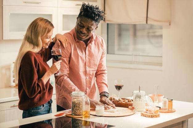 Cintura para cima de uma jovem relaxada tomando vinho tinto na cozinha e colocando uma mão no ombro do namorado enquanto o observa amassando a massa