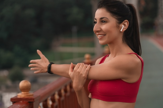 Cintura para cima de uma linda jovem fazendo exercícios de aquecimento enquanto e esticando o braço em uma ponte na cidade