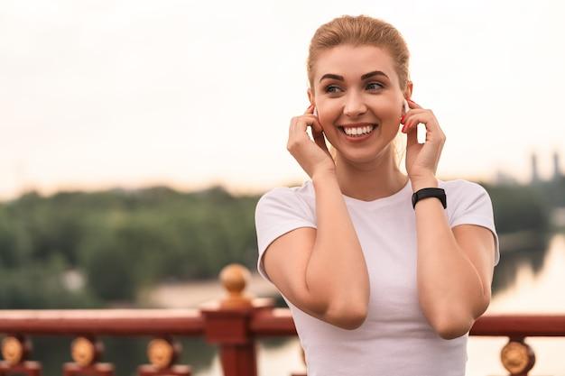 Cintura para cima de uma linda mulher sorridente em uma camiseta branca usando fones de ouvido sem fio em pé na ponte na cidade