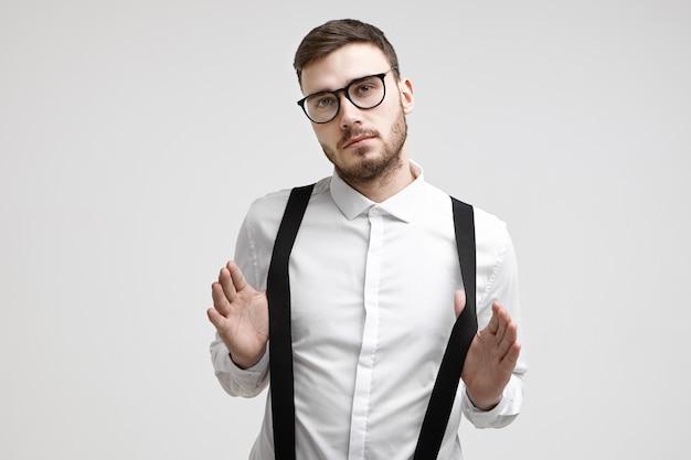 Cintura para cima, foto de um jovem trabalhador de escritório elegante e confiante com a barba por fazer e um corte de cabelo da moda em pé na parede branca usando óculos elegantes e camisa formal, puxando seus suspensórios pretos
