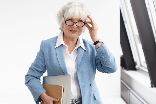 Cintura para cima foto de uma mulher de meia-idade de cabelos grisalhos vestindo elegante jaqueta azul e camisa branca ajustando seus óculos, posando no interior do escritório, carregando laptop e diário a caminho do encontro