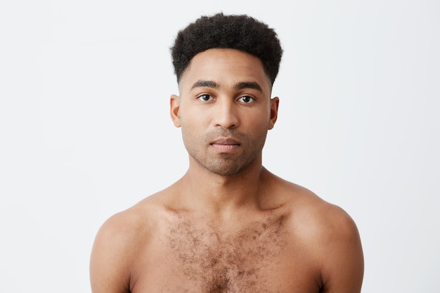 Cintura para cima o retrato da foto do homem africano de raça mista de pele negra com cabelo escuro encaracolado, sem roupa, olhando na câmera com a expressão do rosto relaxado.