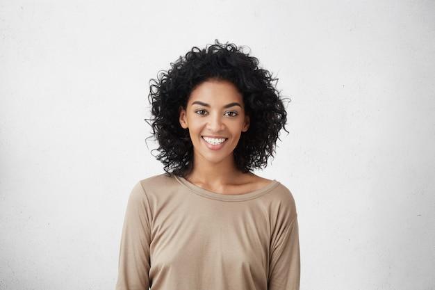 Cintura para cima o retrato de uma fêmea jovem de raça mista, vestida casualmente, com cabelos cacheados, sorrindo alegremente durante a audição para o papel em séries de tv, sentindo-se excitada e muito nervosa, tentando impressionar o diretor