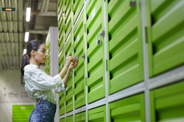 Cintura para cima, retrato com vista lateral de uma bela jovem abrindo o cadeado na porta da unidade de armazenamento automático, copie o espaço