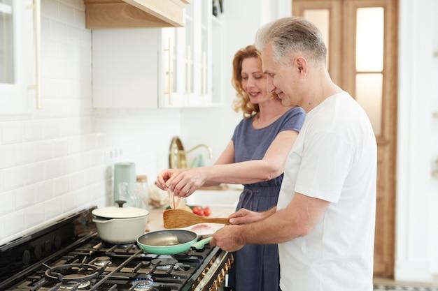 Cintura para cima, retrato de alegre casal maduro fazendo o café da manhã juntos na cozinha de casa com uma mulher elegante quebrando ovos na frigideira, copie o espaço
