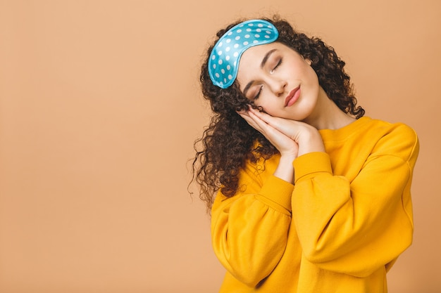 Cintura para cima retrato de alegre jovem sorridente cacheada linda máscara de dormir. isolado em fundo bege
