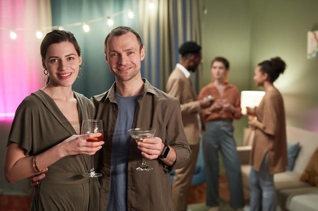 Cintura para cima retrato de casal adulto sorridente, olhando para a câmera e segurando os óculos enquanto desfruta da festa em casa, copie o espaço