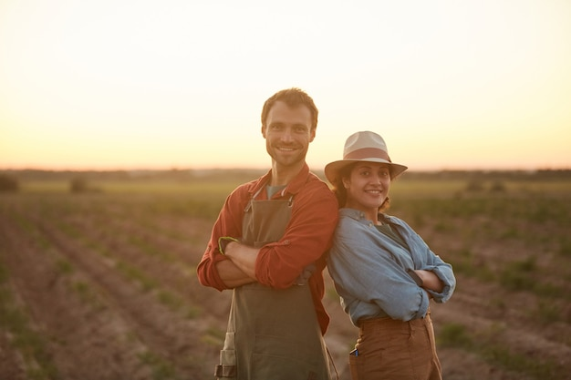 Cintura para cima retrato de casal de jovens agricultores posando de costas um para o outro enquanto está no campo ao pôr do sol e sorrindo para a câmera, copie o espaço