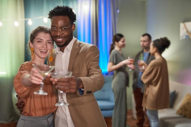 Cintura para cima retrato de casal jovem elegante olhando para a câmera e tilintando de copos enquanto desfruta da festa em casa, copie o espaço