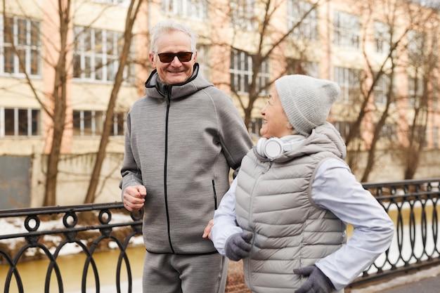 Cintura para cima, retrato de casal sênior ativo correndo ao ar livre no inverno e sorrindo feliz, copie o espaço