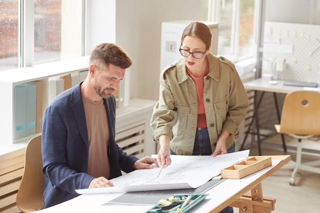 Cintura para cima retrato de dois arquitetos apontando para plantas e discutindo o trabalho em pé, desenhando uma mesa no escritório iluminada pela luz solar,