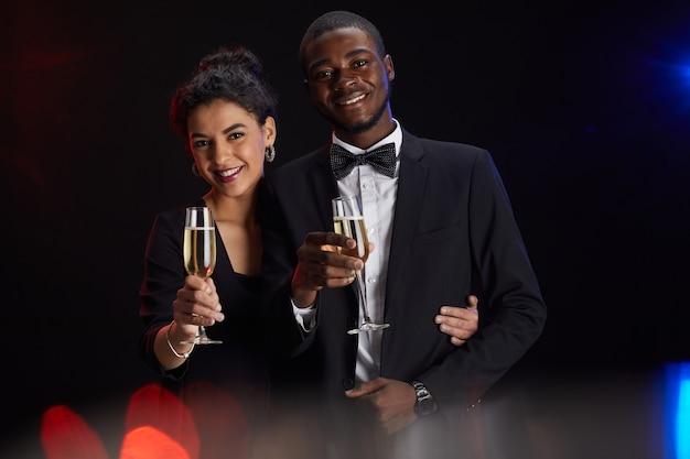 Cintura para cima retrato de elegante casal de raça mista segurando taça de champanhe e sorrindo para a câmera em pé contra um fundo preto na festa, copie o espaço