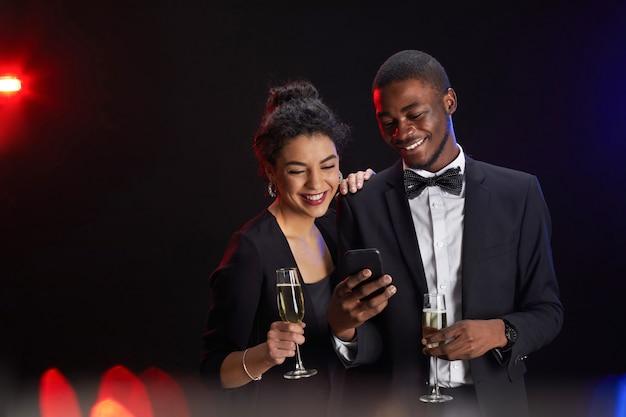 Cintura para cima retrato de elegante casal de raça mista segurando um smartphone e taças de champanhe em pé contra um fundo preto na festa, copie o espaço