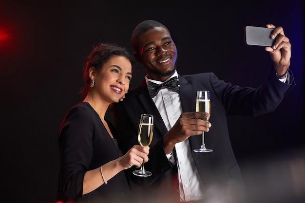 Cintura para cima retrato de elegante casal de raça mista tirando foto de selfie em pé contra um fundo preto na festa, copie o espaço