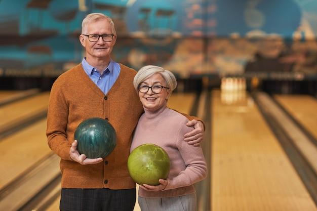 Cintura para cima, retrato de feliz casal sênior segurando bolas de boliche e sorrindo para a câmera enquanto desfruta de entretenimento ativo na pista de boliche, copie o espaço