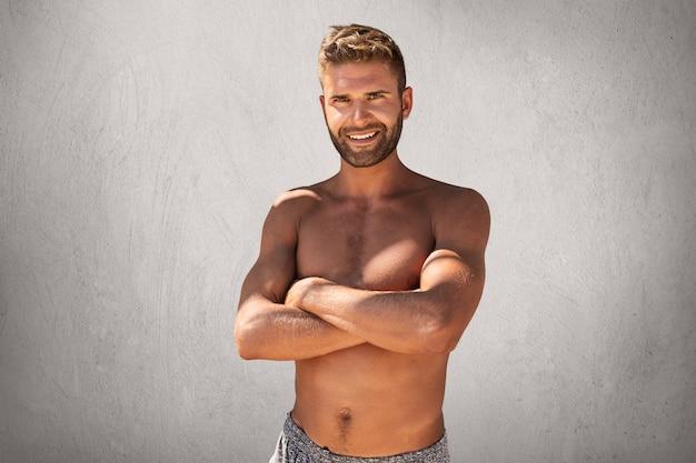 Cintura para cima retrato de homem atraente musculoso com penteado na moda e cerdas, mantendo as mãos cruzadas