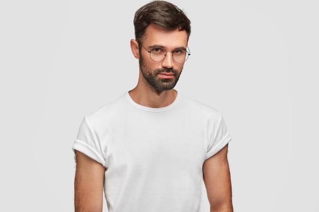 Cintura para cima retrato de homem barbudo bonito com expressão séria, contempla sobre algo, usa óculos redondos e camiseta branca casual, posa dentro de casa. pessoas e expressões faciais