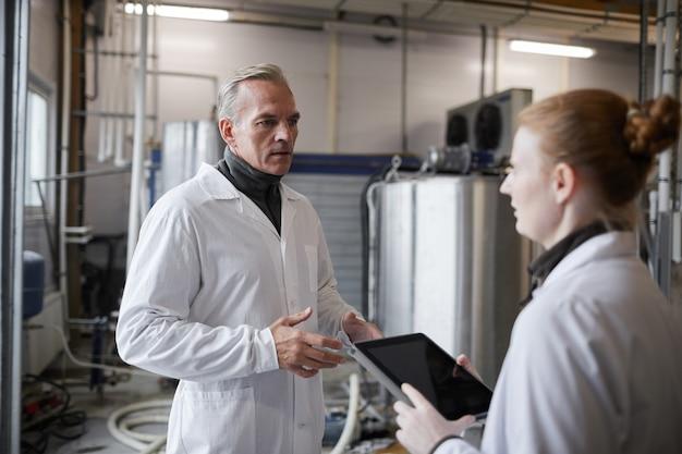 Cintura para cima retrato de homem maduro instruindo trabalhadora enquanto discute o trabalho na fábrica de produção de alimentos, copie o espaço