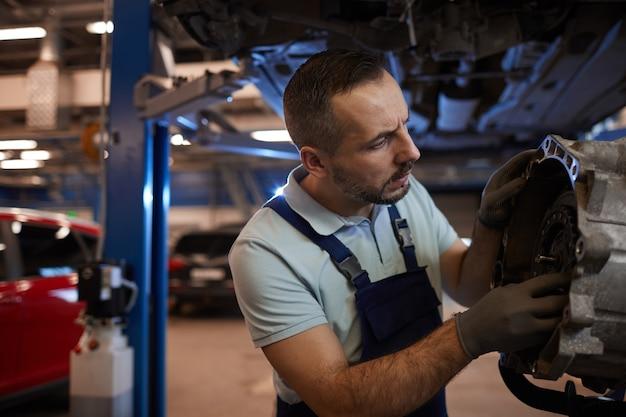 Cintura para cima, retrato de mecânico de automóveis barbudo consertando caixa de marchas em oficina automotiva, copie o espaço