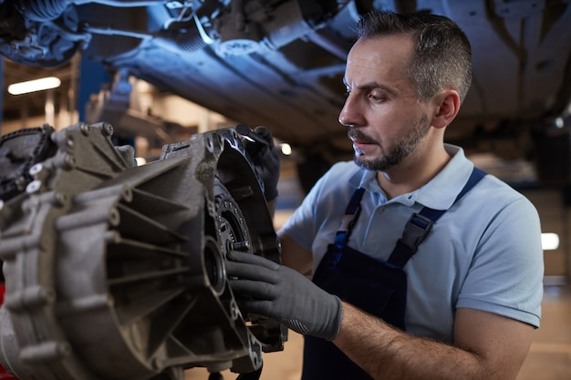 Cintura para cima retrato de mecânico de automóveis musculoso inspecionando peça de carro em oficina mecânica, copie o espaço
