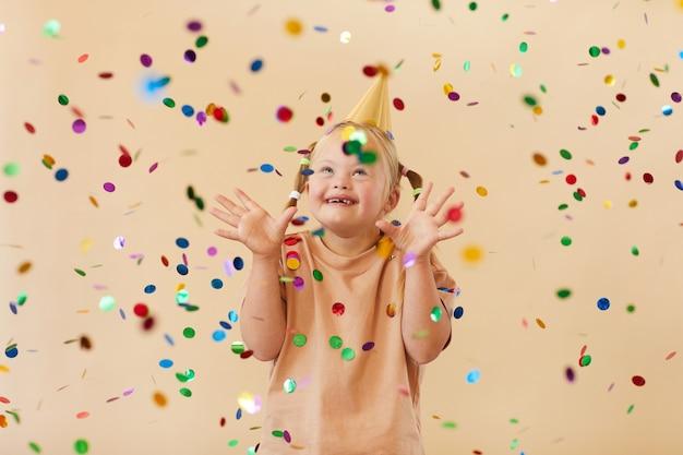 Cintura para cima, retrato de menina animada com síndrome de down sorrindo alegremente enquanto está sob o chuveiro de confete no estúdio, copie o espaço