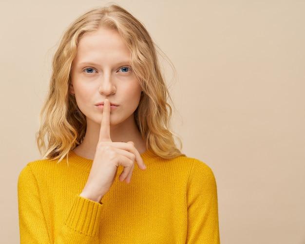 Cintura para cima, retrato de mulher colocando o dedo nos lábios, por favor, não faça barulho, silêncio mantendo segredo