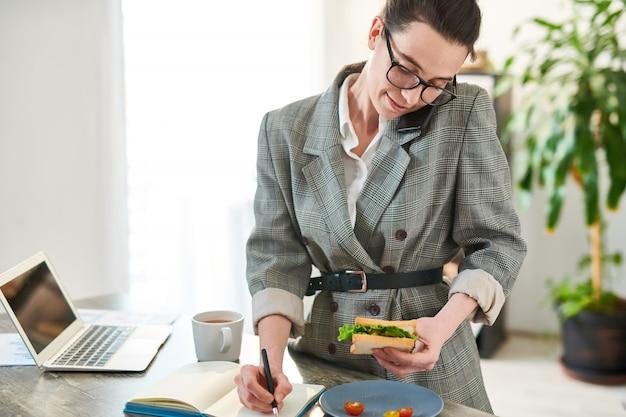 Cintura para cima retrato de mulher jovem ocupada falando por telefone durante a pausa para o almoço no escritório, cópia espaço