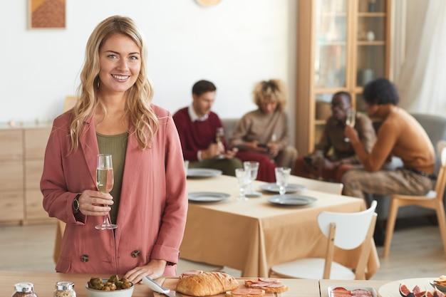 Cintura para cima retrato de mulher loira elegante sorrindo para a câmera e segurando uma taça de champanhe enquanto desfruta de um jantar dentro de casa com os amigos.
