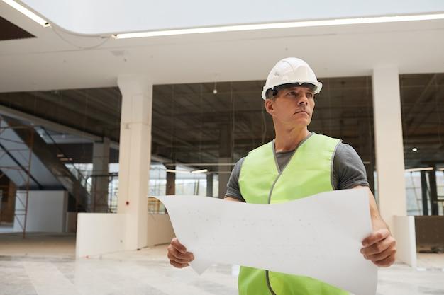 Cintura para cima retrato de trabalhador da construção civil profissional segurando plantas e olhando para longe enquanto está em um prédio de escritórios,