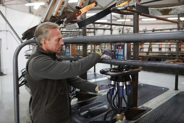 Cintura para cima, retrato de trabalhador maduro configurando máquina de ordenha de vacas em uma fazenda leiteira moderna, copie o espaço